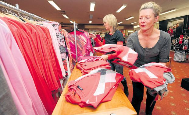 McElhinney's staff members Noleen Ward, left, and Catherine Keane arrange the womenswear display before the store re-opening today. JAMES FLYNN