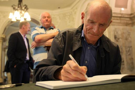 Members of the public queue to sign a book of condolence at Belfast city hall for hometown hero and snooker legend Alex 'Hurricane' Higgins. Photo: PA