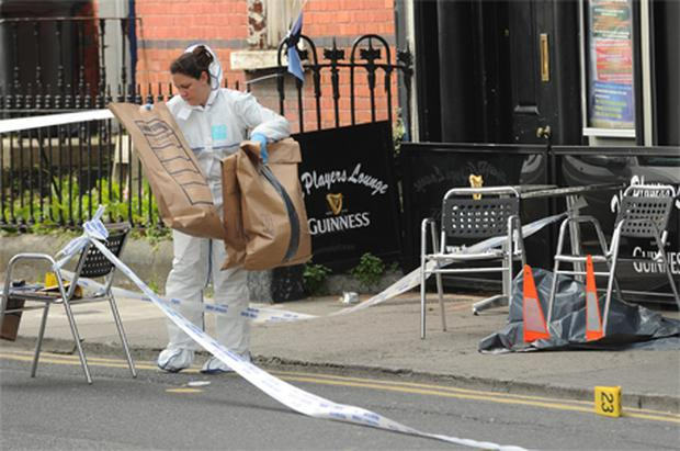 GUN ATTACK: A forensics officer gathers evidence outside the Players Lounge on Fairview Strand, Dublin, where the doorman and two customers were shot last week