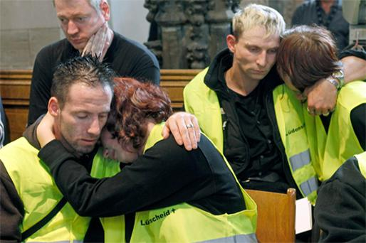 GRIEF: Members of the rescue services at a memorial service for the 21 people killed at the Love Parade last week