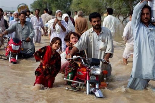 A man evacuates his children through waist-deep waters after heavy flooding in Nowshera in Pakistan's northwest Khyber-Pakhtoonkhwa Province yesterday