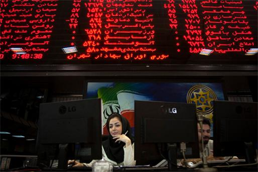 An Iranian official works at her desk in the main hall of the Tehran Stock Exchange yesterday