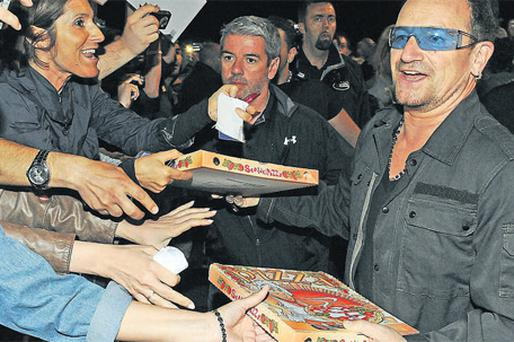 Bono joins U2 crew members before their show in Turin to pass out pizzas to those fans who turned up early to listen to the band's rehearsals