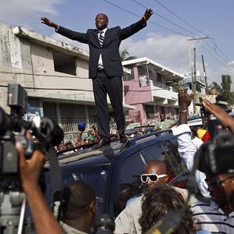 Wyclef Jean greets supporters from the top of a vehicle after applying to run for president of Haiti (AP)