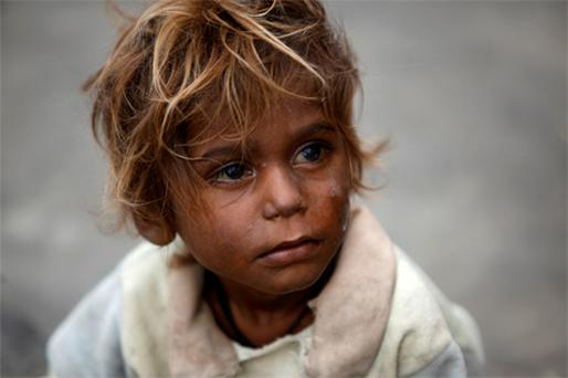 Anxiety etched on his face, a little boy awaits food aid in a village in Sukkur, in the Sindh province of Pakistan, yesterday