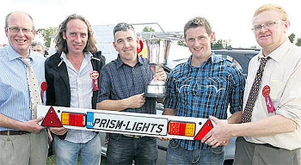 Tullamore Show's Rodney Cox, Tony Garvey, Seamus McGovern and Rory Cullen, and Farming Independent's Bruce Lett display the trophy for the show's winning invention, the Prism Wireless Lights - a set of cableless trailer lights