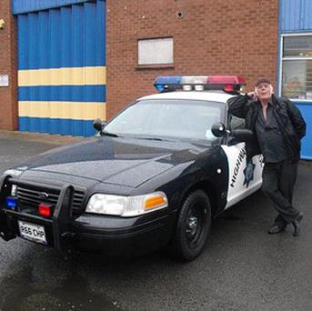 Malcolm Gibbs with his decommissioned 1999 Ford Crown Victoria US police car