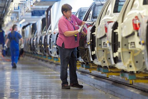 A worker assembles a Mercedes Benz E-Class automobile on the production line in Daimler AG's Mercedes factory in Stuttgart