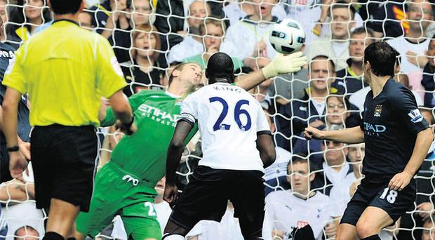 Manchester City's goalkeeper Joe Hart makes a diving save from Tottenham Hotspur's Jermain Defoe (out of picture) during yesterday's Premier League match at White Hart Lane. Photo: Dylan Martinez