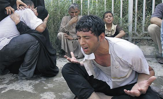 Residents mourn as they wait to claim the bodies of bomb attack victims outside a morgue in Baghdad, yesterday