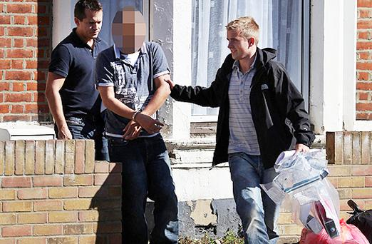 A man is arrested by police officers at an address in Southend, England, as officers shut down a global criminal conspiracy Photo: PA
