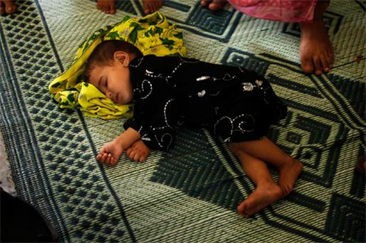 One-year-old Naeema, who has a heart condition, lies asleep at her mother's feet at a college converted into emergency shelter in Charsadda, Khyber-Pakhtunkhwa Province