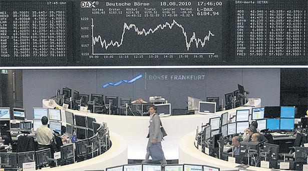 Traders work at their desks in front of the the DAX board at the Frankfurt stock exchange yesterday