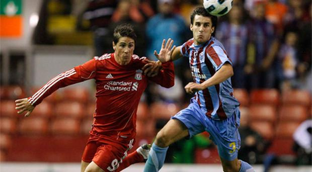 Fernando Torres challenges Trabzonspor's Hrvoje Cale during the Europa League tie at Anfield last night