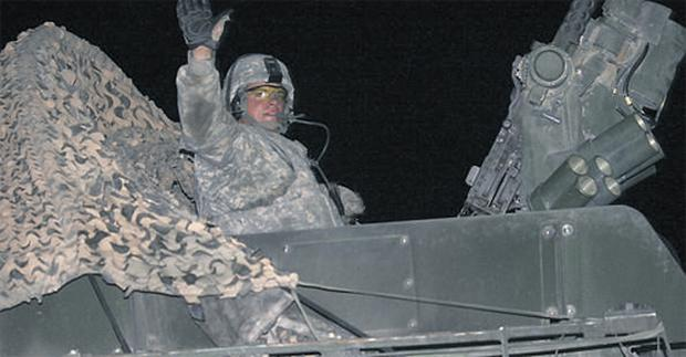 A US soldier with the 4th Stryker Brigade, 2nd Infantry Division, waves as he and fellow soldiers roll across the Iraqi border into Kuwait early on Monday morning