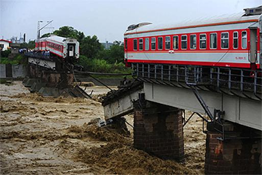 The front and rear coaches of a passenger train sit on the half-destroyed Shitingjiang Bridge, on the Baocheng Railway, in Guanghan City in south-west China's Sichuan Province