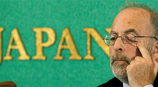 Central Bank governor Patrick Honohan rubs his eye during a news conference in Tokyo yesterday where he said the Irish banking system has improved a lot but that high yields on Irish government debt have not dissipated