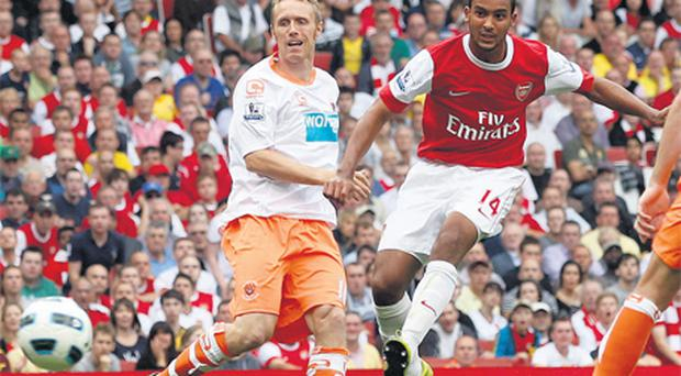 Arsenal's Theo Walcott shoots and scores his third goal against Blackpool at the Emirates Stadium yesterday