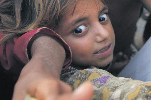 Children wait for food at a camp in Punjab province, Pakistan, yesterday