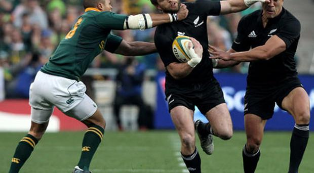New Zealand's Cory Jane is tackled by Juan de Jongh of South Africa as Mils Muliaina watches on during Saturday's Tri-Nations game. Photo: Getty Images