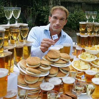 Dr Christian Jessen is surrounded by food and drink to illustrate the amount the average British person has consumed during BBQs and pub visits this summer