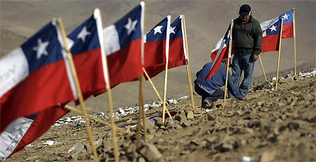 Carlos Araya and Jorge Galleguillos place a Chilean flag with the name of their relative Carlos Galleguillos, one of the 33 miners trapped at the San Jose collapsed mine. Photo: AP