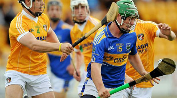 John O'Dwyer, Tipperary, in action against Stephen Shannon, 4, and Kevin Molloy, Antrim. Photo: Ray McManus / Sportsfile