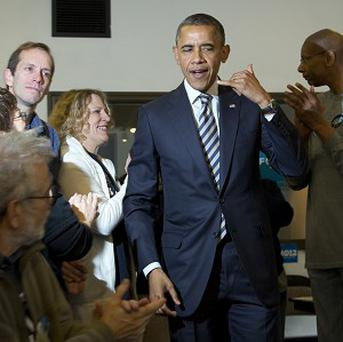 Barack Obama gestures during a visit to a campaign office in Chicago on the morning of the election (AP)