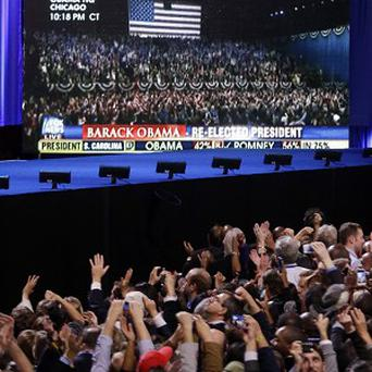 Supporters cheer as CNN projects the re-election of President Barack Obama at his election night party (AP Photo)