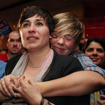 Lauren Snead, right, hugs her partner Katy Jayne as they celebrate the legalisation of same-sex marriage in Portland, Maine (AP)