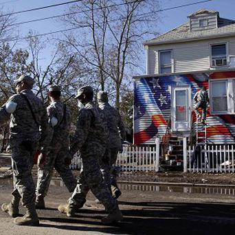 Members of the National Guard patrol near a house damaged by Superstorm Sandy in Staten Island, New York (AP)