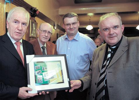 Arts Minister Jimmy Deenihan, former 'Evening Press' editor Sean Ward, the owner of Mulligan's Pub, Gary Cusack, and photographer Liam Mulcahy with the photographic tribute to the late Con Houlihan