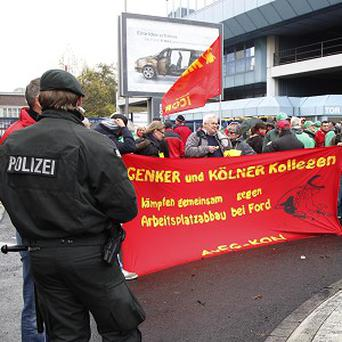 Employees protest against the planned closure of a Belgian factory in front of the Ford plant in Cologne, Germany (AP)