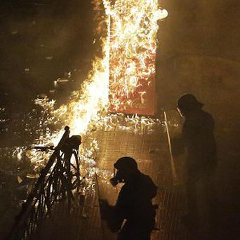 A petrol bomb thrown by protesters explodes near riot police in front of parliament during clashes in Athens (AP)