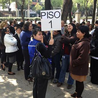 People who work in a seven-storey office building meet after evacuating in Mexico City (AP)