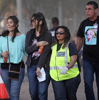 A injured woman, second left, is escorted from the scene of a scaffolding collapse outside a Linkin Park concert in Cape Town (AP)