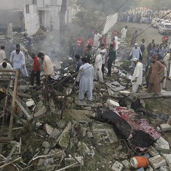 Pakistani investigators gather at the site of an explosion in Karachi (AP)