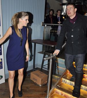 Amy Huberman watches her husband Brian O'Driscoll come down stairs in a cast during her book launch