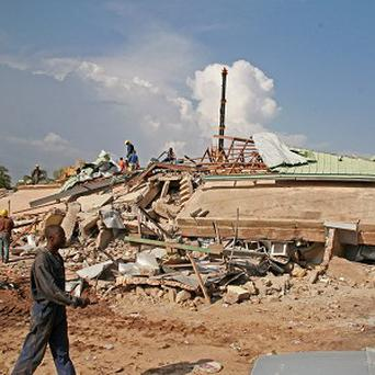 Workers search the debris of a collapsed shopping centre in Accra, Ghana (AP)
