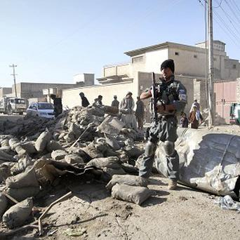 An Afghan policeman stands guard at the scene of a suicide attack in Kandahar (AP)