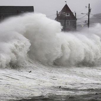 Waves crash into a seawall and buildings along the coast in Hull, Massachusetts as storms hit the US East Coast (AP)