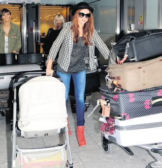 Una Healy arrices at Heathrow airport pushing luggage and daughter Aoife Belle.