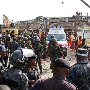 Ghana troops provide security as rescue workers clear rubble from the remainder of a collapsed building in Accra (AP)
