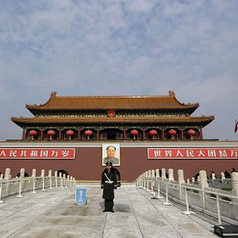 A Chinese paramilitary policeman stands guard in front of Tiananmen gate in Beijing (AP)