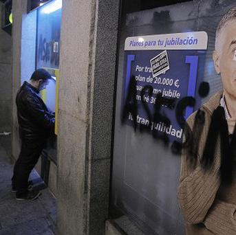 A man uses an ATM as graffiti reading ''Assassins'' is seen in the window of a bank during a march against evictions, in Madrid (AP Photo)