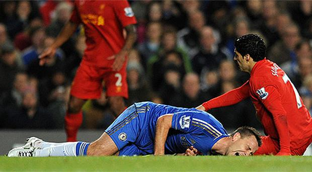 John Terry lies in agony on the ground after picking up a injury in a collision with Liverpool's Luis Suarez