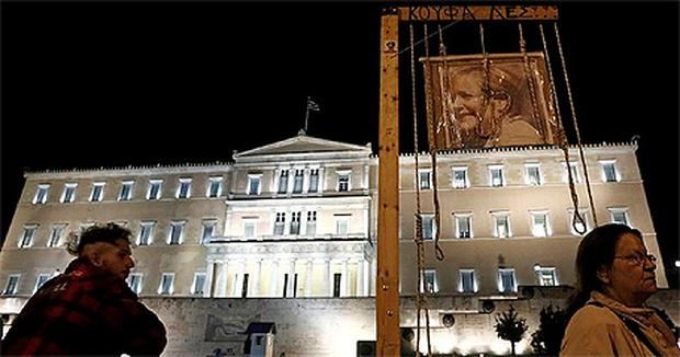 A picture of German Chancellor Angela Merkel appears outside the Greek parliament in Athens