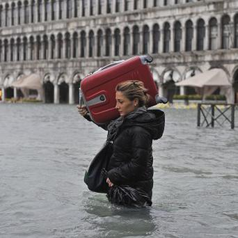 A tourist crosses flooded St Mark's Square in Venice, Italy (AP)