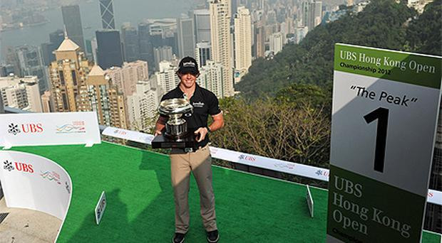 Rory McIlroy poses with The 2012 UBS Hong Kong Open trophy