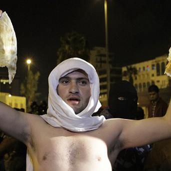 A Jordanian man holds up a piece of bread during protests over rising fuel prices, including a 53% hike on cooking gas (AP)